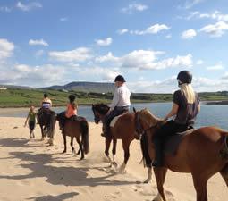 eine Gruppe von Reitern beim Strandausritt in Irland