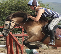 Girl jumping over a jump on horse at Island View Riding Stables